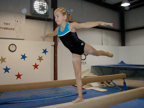 A girl doing a scale on the beam.